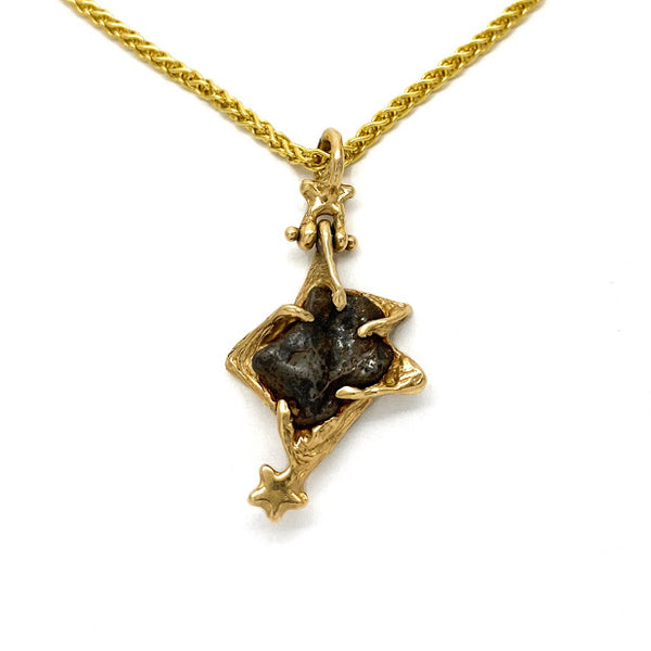 Star shaped pendant set with an Odessa Texas Meteorite and accented with gold stars