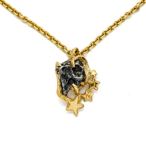 Heart shaped pendant set with an Odessa Texas Meteorite and accented with gold stars