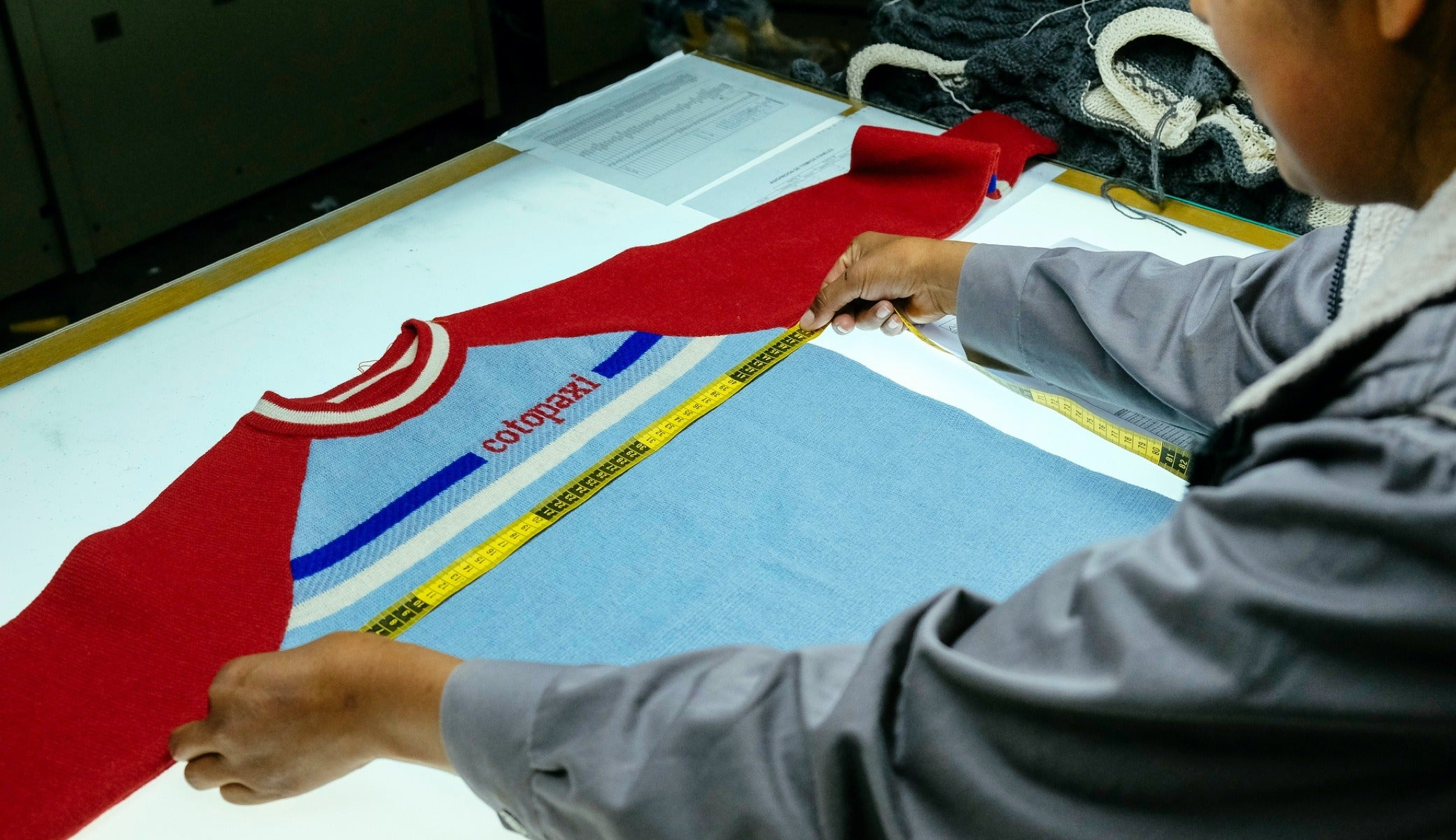 An employee conducts quality assurance tests on a Cotopaxi Libre sweater.
