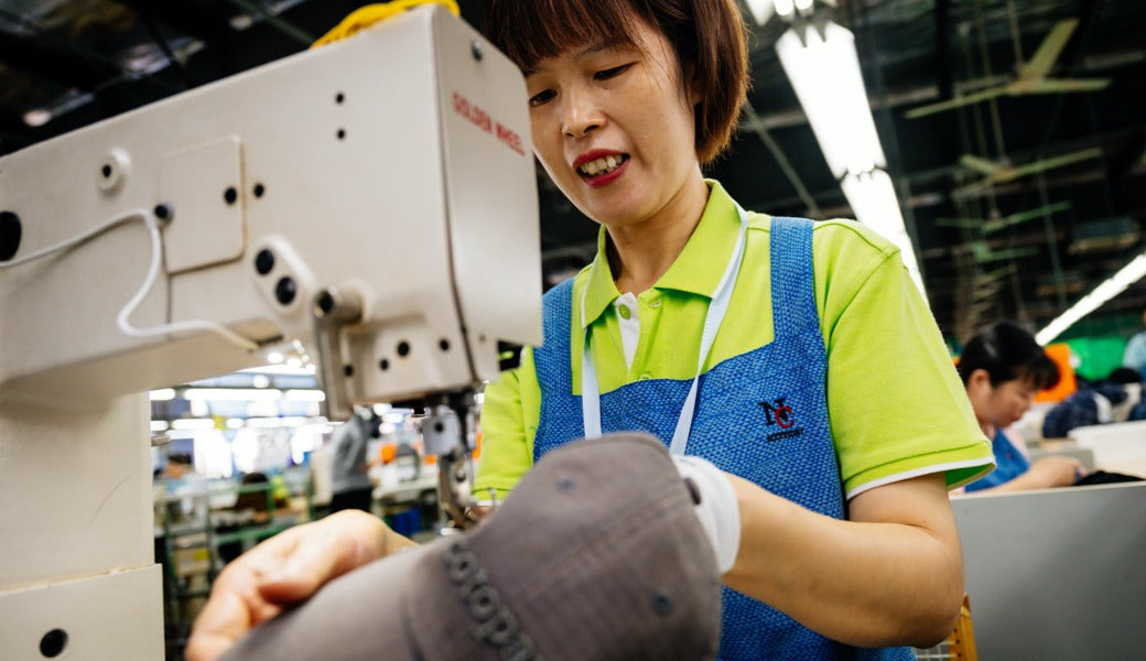 Fang Qiong Xie sews a Cotopaxi hat at ASI factory in Shanghai.