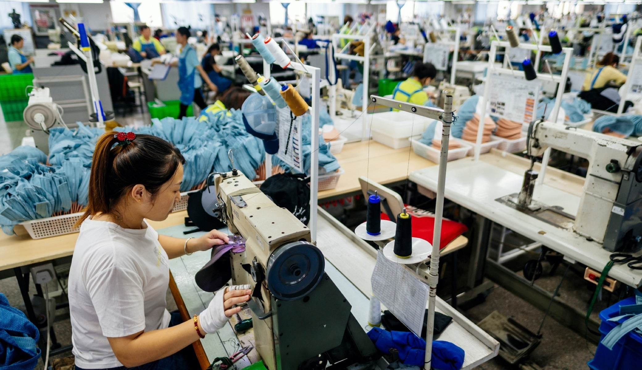 Qian Qian Wei sews on the factory floor at ASI in Shanghai.