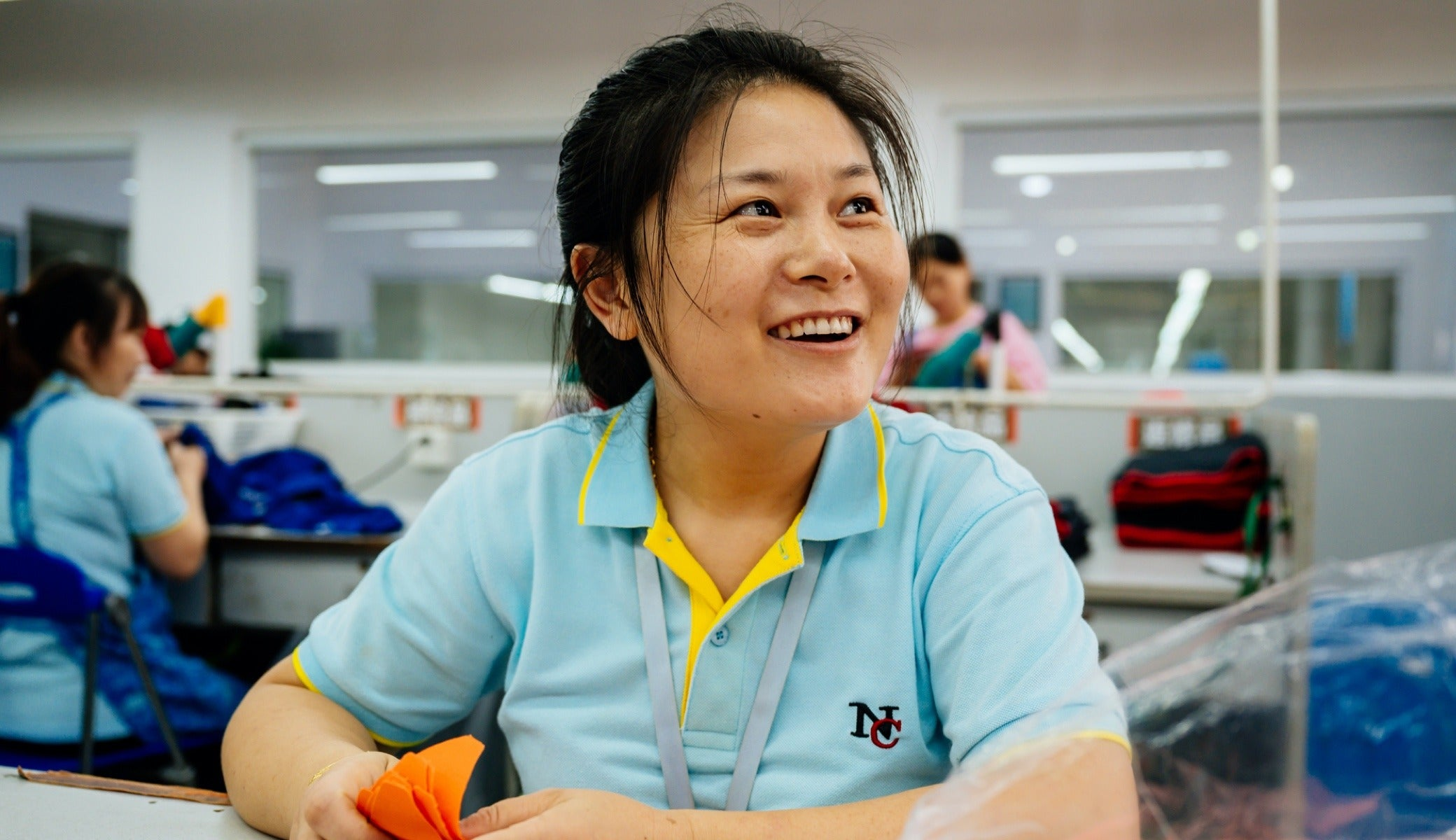 Chun Lin Li, an employee on the embroidering line, was able to save more money for her family after receiving a grocery store gift certificate from the Fair Trade committee.