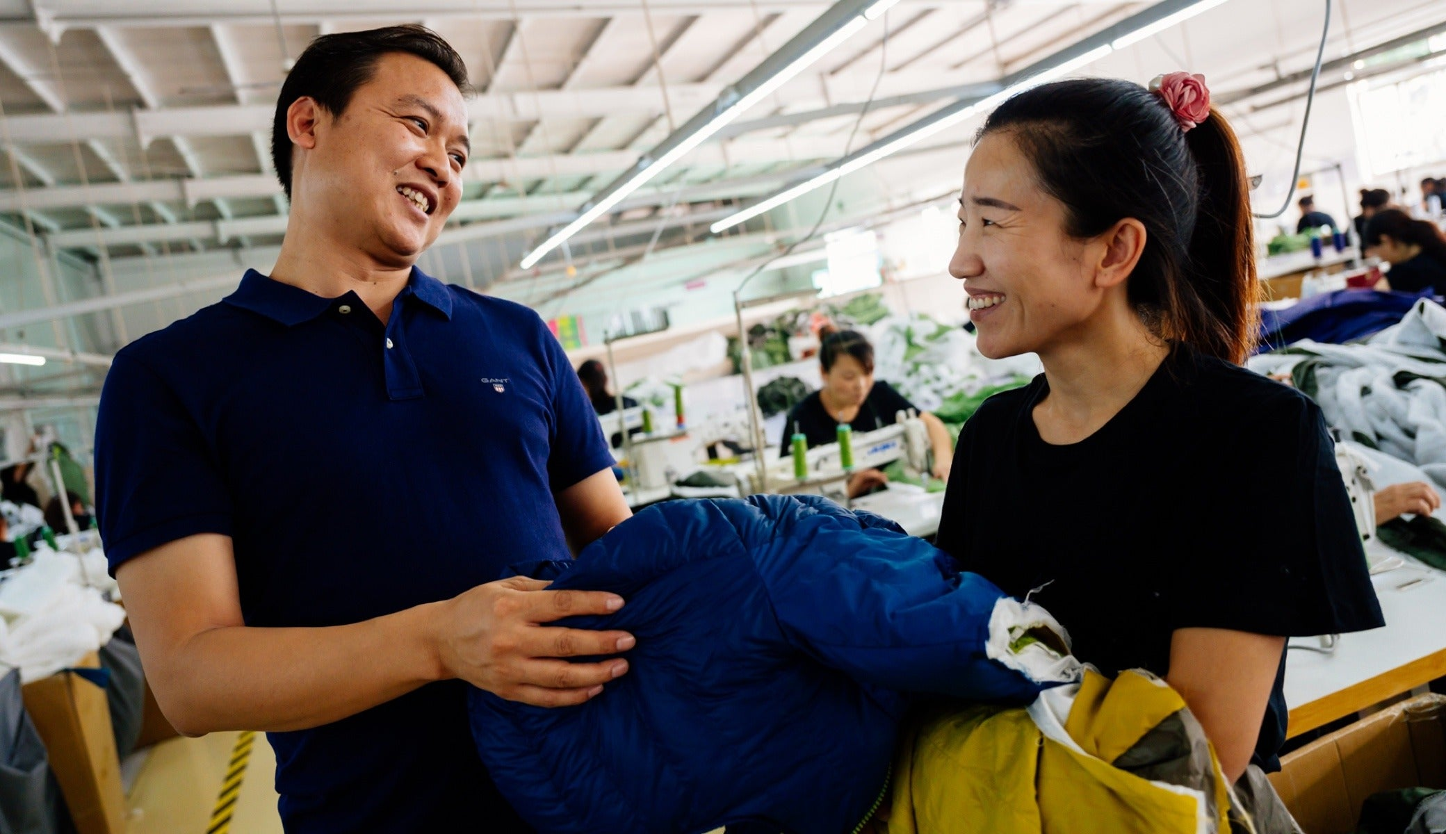 Owner George Huang, left, laughs with employee Song Xiao Ying at the factory outside of Tianjin