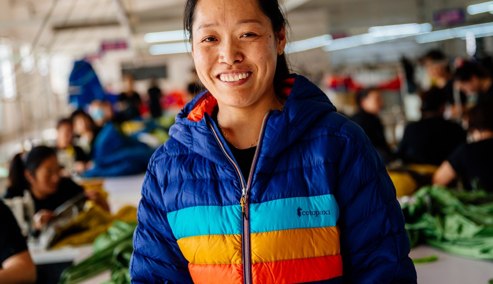 Li Xiu Zhen wears a Cotopaxi Fuego jacket on the sewing floor