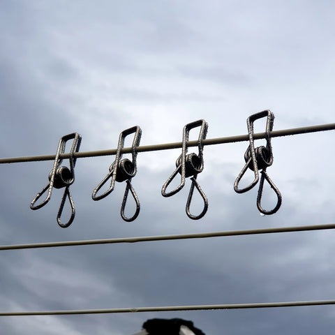 Four stainless steel wire pegs on the clothes line on a grey, cloudy day with water droplets on them.