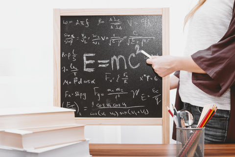 person writing complex formulas on a blackboard