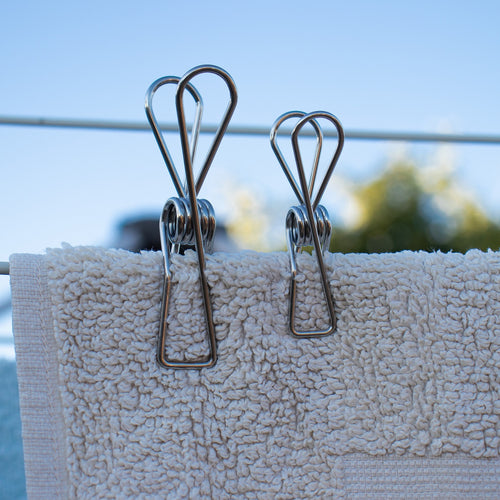 two wire clothes pegs holding up a towel on the clothesline