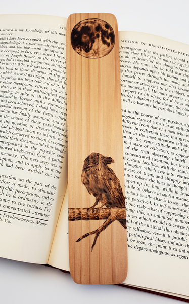 Wooden Bookmark featuring a raven on a branch with a full moon above it.