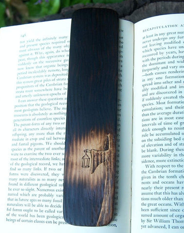 A photo of a woodburned bookmark resting on a book with a leafy background. The bookmark is burned mostly black, with a cloaked figure with a shadowed face holding a lantern that casts an eerie pool of light.