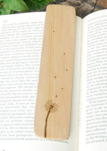 A photo of a bookmark laying on an open book with a leafy green background. On the bookmark is burned an image of a dandelion flower gone to seed, with some seeds floating free in the wind.