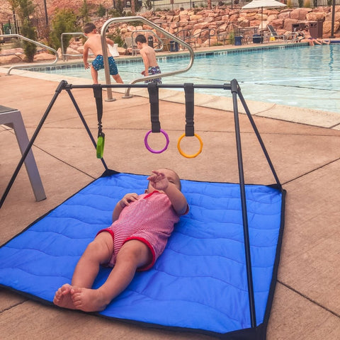 Baby laying on Lay and Play Adventure Mat on pool deck