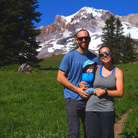 Parents and baby standing in front of mountain