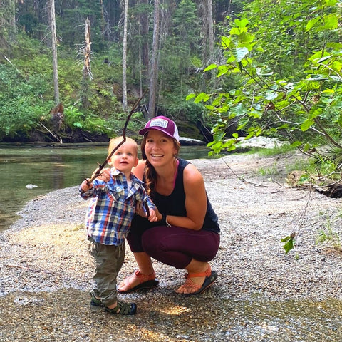 Mom kneeling down by little boy on river bank