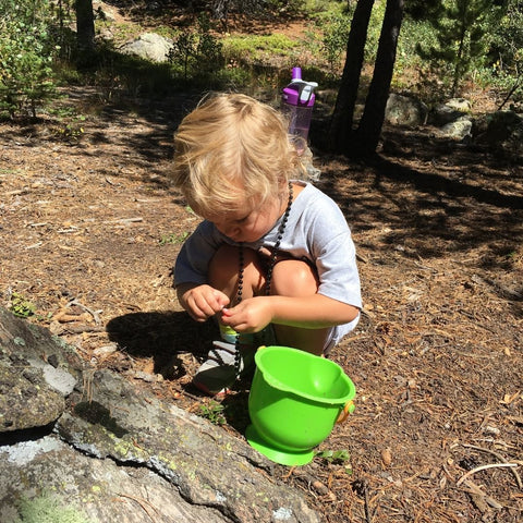Toddler playing in dirt with bucket on hiking trail