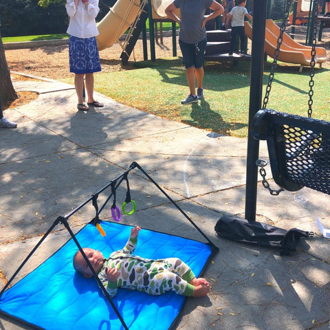 Baby at playground laying on blue Lay and Play Adventure  Mat