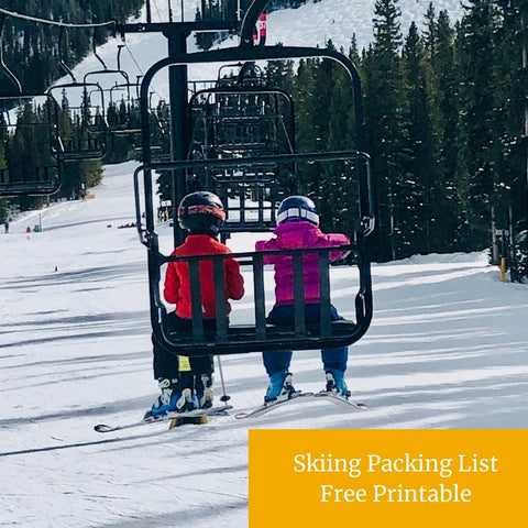 Two kids sitting on a ski chairlift
