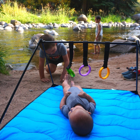 Baby on Lay and Play Adventure Mat, two older brothers in the background playing in river