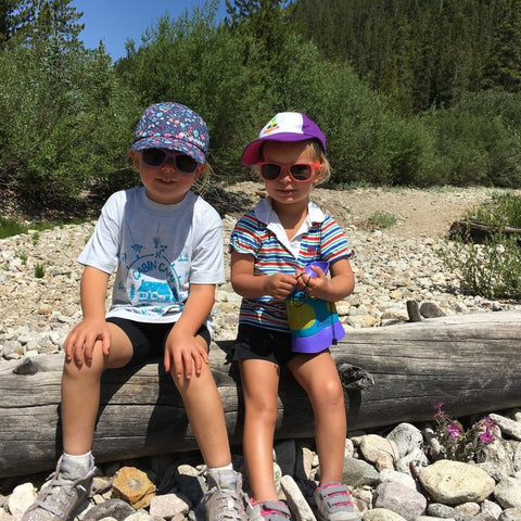 Two small kids sitting on log wearing hats and sunglasses