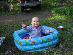 Baby in an inflatable pool without water