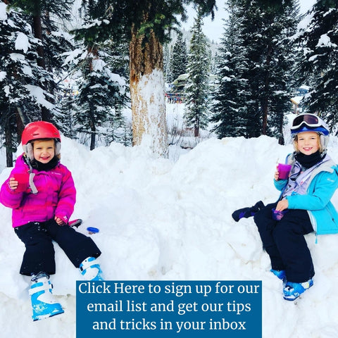 Two girls sitting in ski clothes in snow.