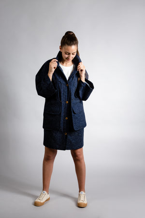 Long denim jacket with buttons and two flap pockets.