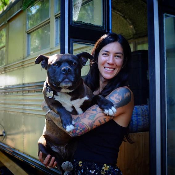 Tiny Life Supply ambassador Tia Scheffer holding her dog in front of her DIY school bus conversion.