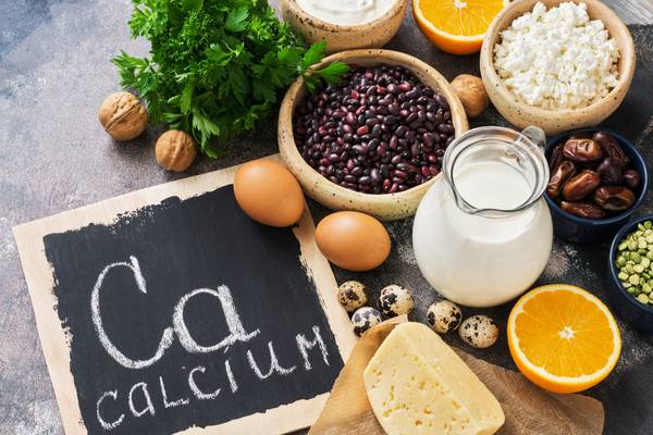 A variety of foods rich in calcium and signboard with the word calcium