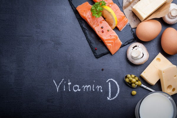 Black slate table with product rich in vitamin D and omega 3. Written word vitamin D by white chalk.
