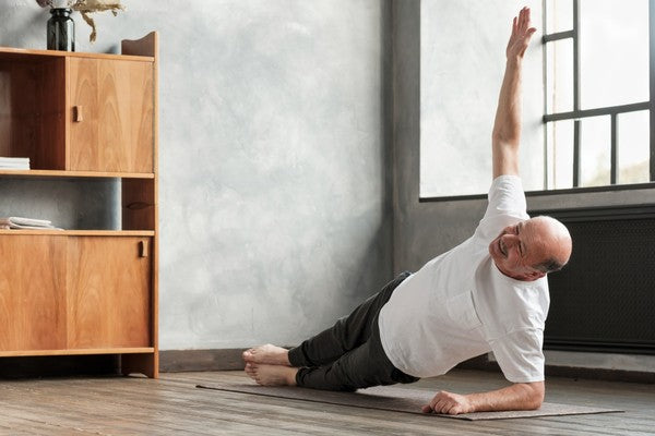 Cheerful senior hispanic man doing a side plank exercise at living room.