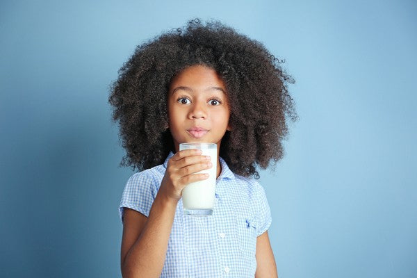 Cute girl with curly hair drinking milk on a blue background