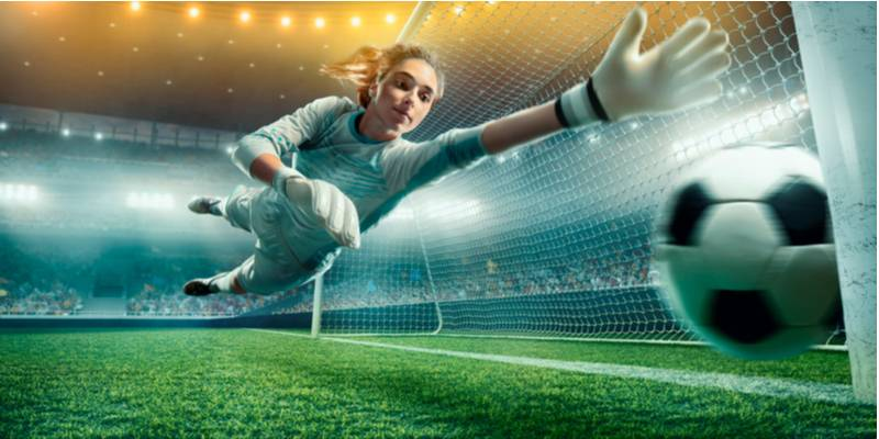 Female Soccer Goalkeeper catch the ball on a professional soccer stadium