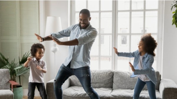 Happy father dances with his daugthers in the living room