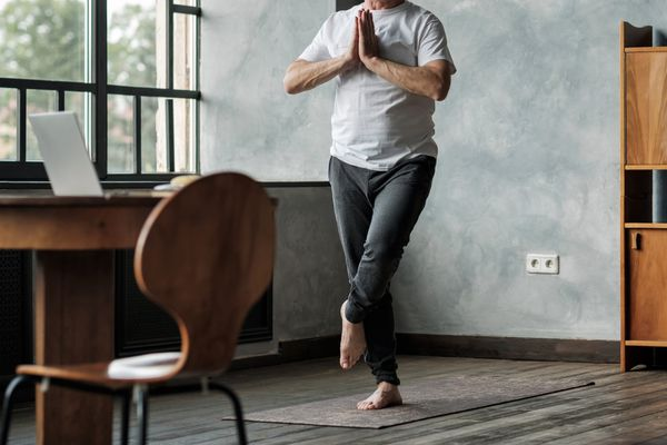 Man standing in one leg yoga balance variation. No face view