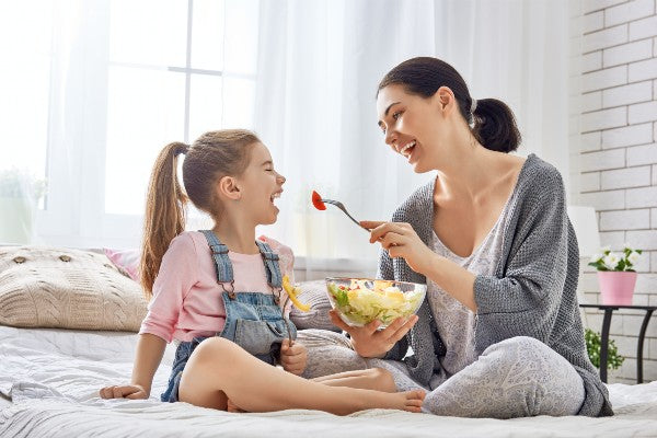 Mother and her daughter child girl are eating salad on the bed in the room