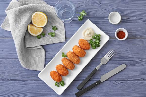 Plate with delicious croquettes on table