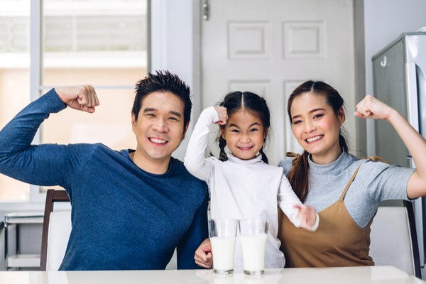 Portrait of enjoy happy love asian family father and mother with little asian girl smiling look at camara and having breakfast drinking and hold glasses of milk at table in kitchen