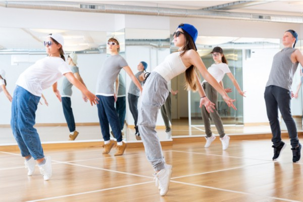 Positive teenage girls and boys training hip hop in dance studio
