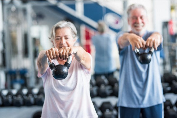 Senior couple doing shoulder lifts with weights in gym