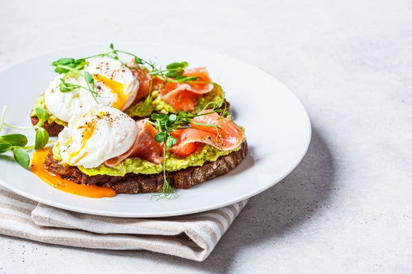 Toast with salmon, poached egg and avocado on a white plate.