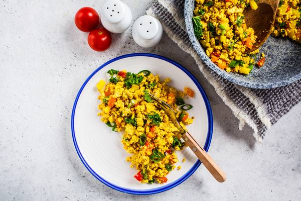 Tofu scramble with vegetables on white plate