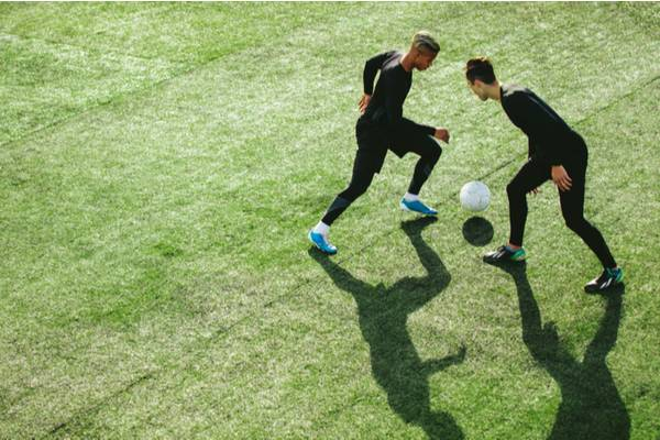 Top view of two teenagers playing football during team practice in field