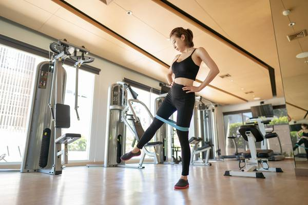 Woman training legs muscles, doing side leg raise with elastic band in gym