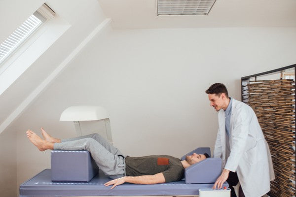 Young Caucasian medical technician operating the bone densitometer while his patient is lying on the bed.