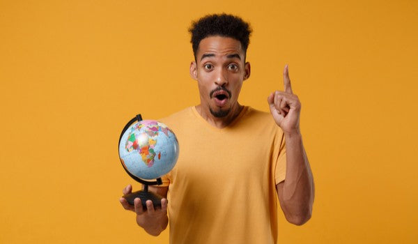 Young african american in casual t-shirt holding globe and pointing index finger up