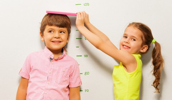 Young boy and girl measure height by wall scale at home