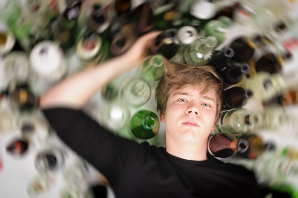 Young man with short blond hair lying on the floor and is surrounded by many empty beer and liquor bottles, upper perspective