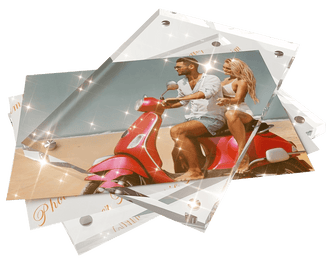 Inserting Photos to the Kluger Punkt Photo Frame. Two crystal clear glass blocks with two photos back-to-back inside. One photograph shows an attractive couple riding an Italian bike on a beach.