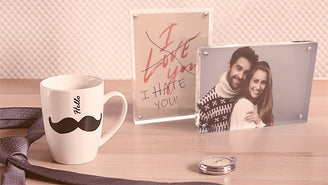 Two Kluger Punkt photo frames on a table next to a mug with a mustache on it and a tie. One photo showing a couple and another text