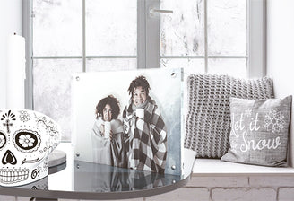 Kluger Punkt photo frame on a glass table with a funny skulp and a candle on it and next to a frozen window and a pillow with text: