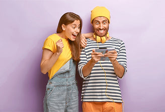 A couple in funny clothes surprised and amuzed by some photo in a Kluger Punkt photo frame.